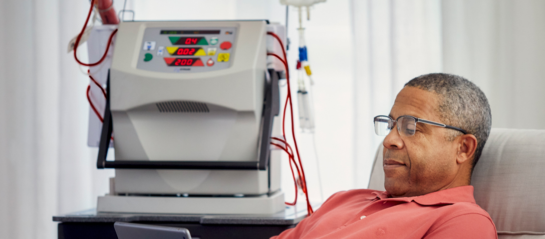 Man reading tablet while undergoing Dialysis