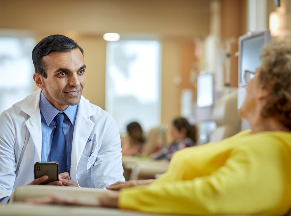 Doctor Interacting With Tablet Software And Phone