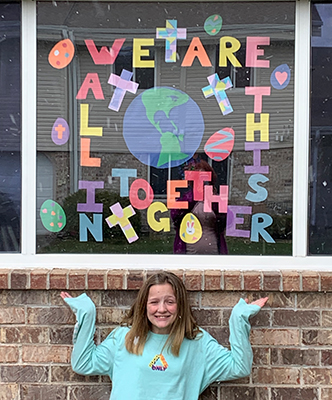 "Girl displaying window art that reads, ""We are all in this together."""