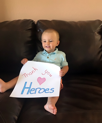 Remington holds up a card thanking the heroes at Fresenius Medical Care.